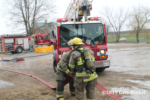 Firefighters connect hose at fire scene