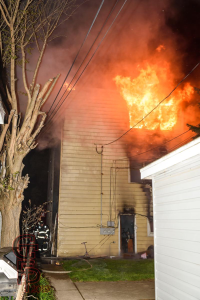 fire erupts from rear apartment window at night