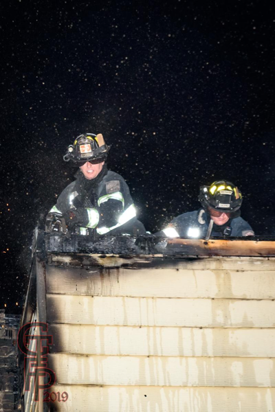 Firefighters om roof of fire building at night