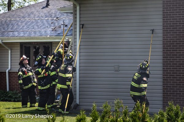 Firefighters use four pike poles to pull soffits