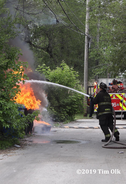 Firefighter attacks alley garage fire with a hose line