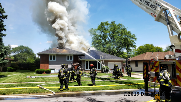flames and smoke through roof of house on fire