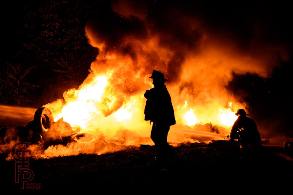 Firefighters extinguishing a pile of tires burning at night