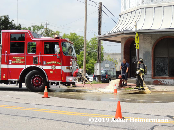 Firefighters flush hydrant at fire scene
