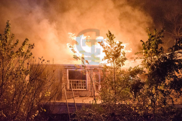 dramatic photo of house fire at night