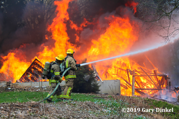 Firefighters with hose battle flames