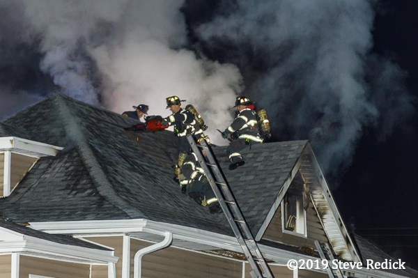 Firefighters vent a roof at night