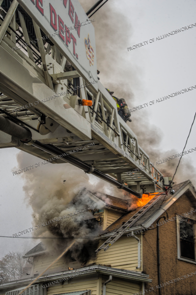 Firefighters retreat down aerial ladder at fire
