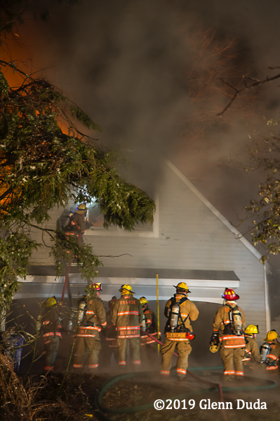Firefighters battle house fire at night
