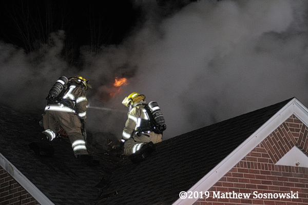 Firefighters on roof of house in smoke