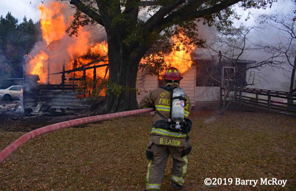 Firefighter with hose battles house fire