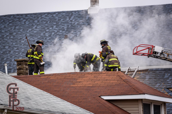 Chicago Firefighters vent the roof of a house on fire