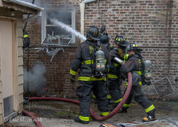 Firefighters deploy a hand line at fire