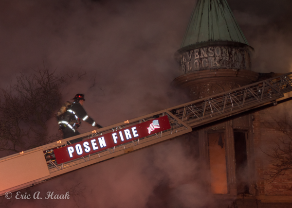 Firefighter climbs aerial ladder at night