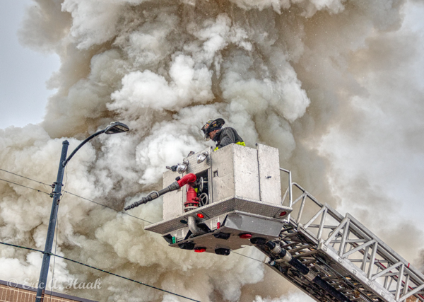 Firefighters in tower ladder basket with heavy smoke