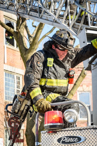 Firefighter in PPE carries power saw
