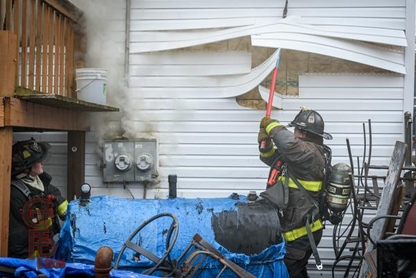 Firefighter pulls siding from house