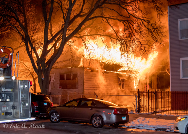 flames engulf the roof of a house at night