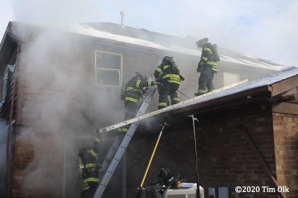 Firefighters on the roof of a house with snoe