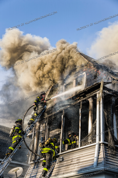 Firefighters battle house fire from a ladder