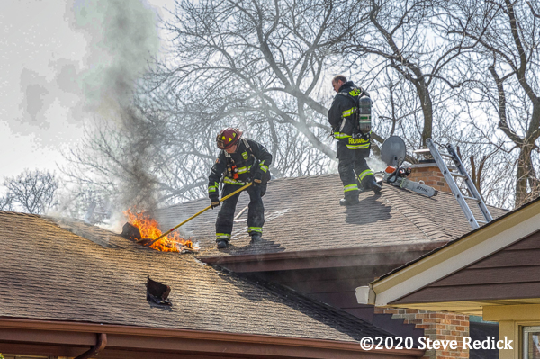 Firefighters on roof with attic fire