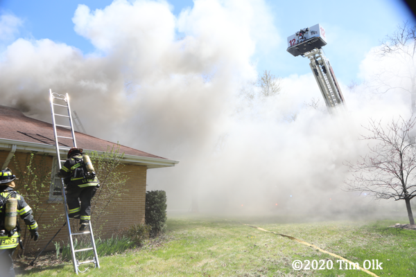 Firefighters climb ladder at house fire