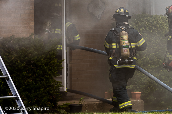 Firefighters enter house on fire with hose
