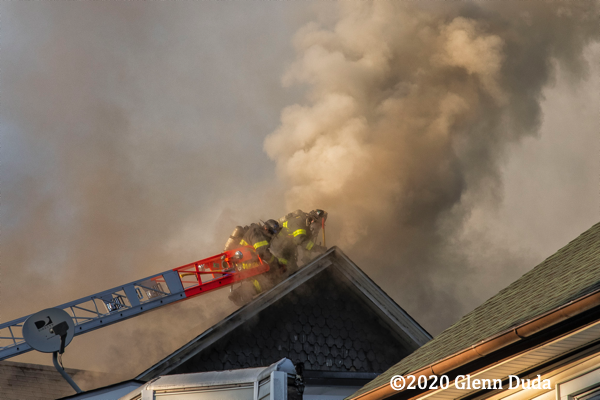 heavy smoke from roof of house on fire
