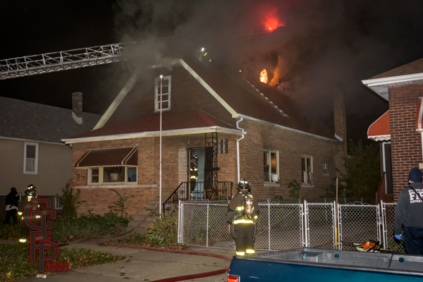 smoke and flames from the roof of a house at night