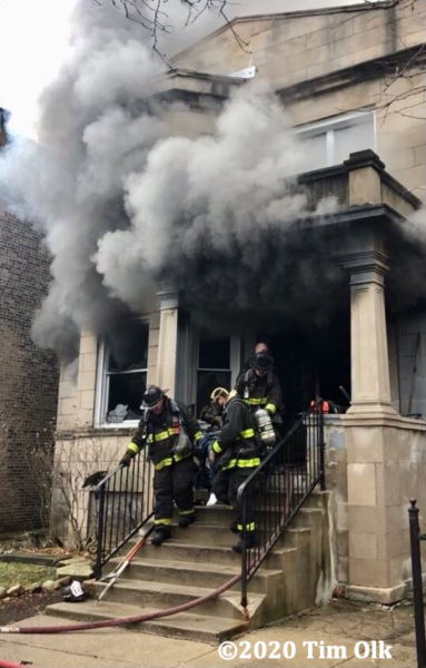 Firefighters carry victim from house on fire