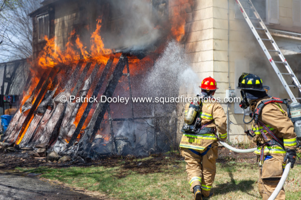 Firefighters advance a hose line on a house fire