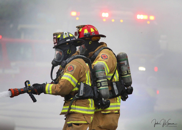 Firefighters in full PPE with hose line