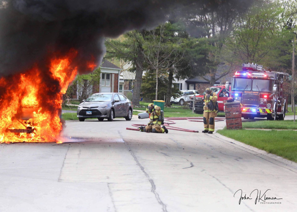 Firefighters in Buffalo Grove prepare to extinguish a minivan on fire
