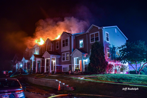 flames through the roof of a townhouse