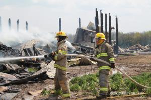 firefighters at barn fire aftermath