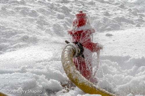 hose on fire hydrant in winter with frozen spray