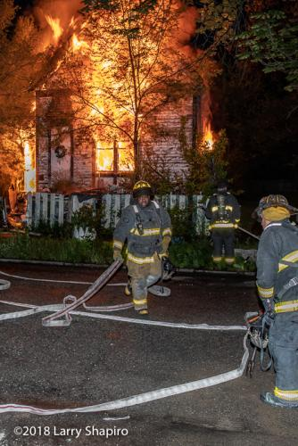 Firefighters at the scene of a house engulfed in flames at night