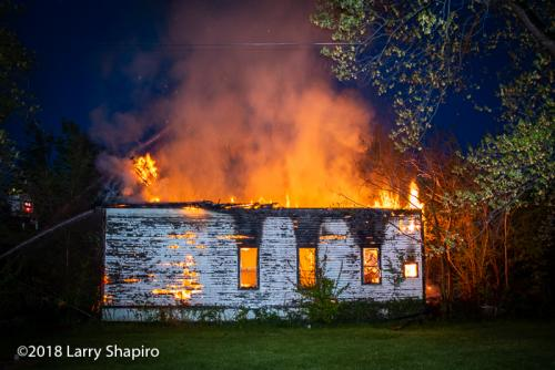 house engulfed by flames at dawn