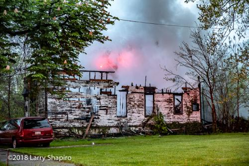 smoke rises from house destroyed by fire at dawn