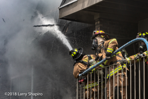 Firefighters with hose battle building fire