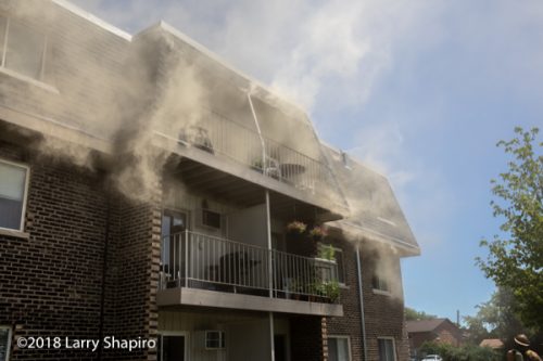 smoke pushes from attic and windows of building on fire