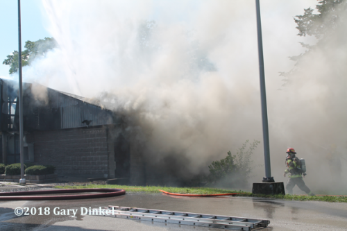 heavy smoke pours from commercial building fire