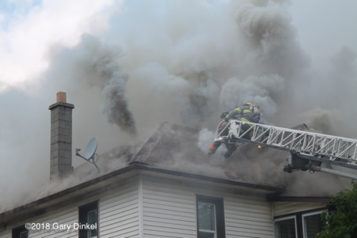Firefighters at aerial ladder tip on roof with heavy smoke