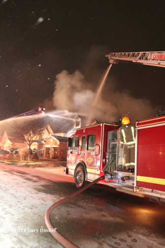fire truck battling house fire at night