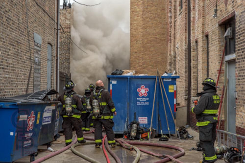 heavy smoke pushes into alley from building fire