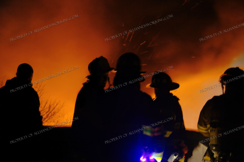 Firefighters silhouetted against fire at night