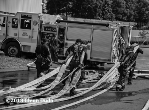 Firefighters drag hose after a fire