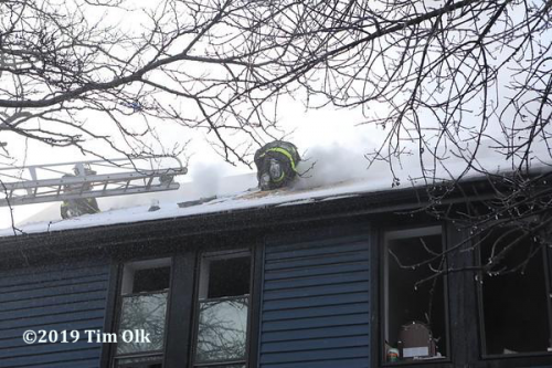 Firefighter on roof of house on fire